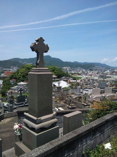 写真・図版 : 爆心地方向を望む共同墓地。墓石に十字架の墓は浦上に多い