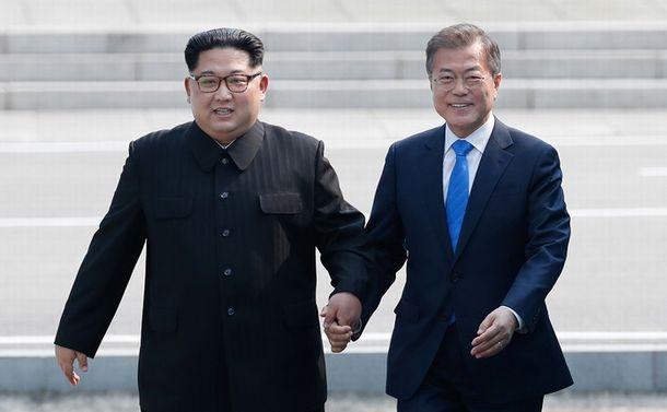 写真・図版 : 板門店の軍事境界線を一緒に越える韓国の文在寅大統領(右)と金正恩朝鮮労働党委員長=2018年4月27日、韓国共同写真記者団撮影
