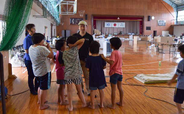 避難所となっている愛媛県の野村中学で子どもたちと話すJPFのスタッフ。話の中からニーズを聞き取る=2018年7月14日