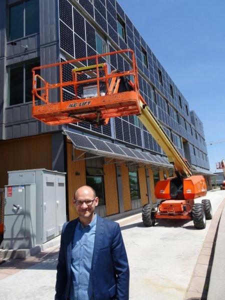 ロッキーマンテン研究所のボドナーさん。ボールダー研究棟の東壁面は太陽光パネルに覆い尽くされている。