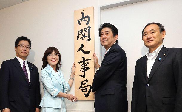 写真・図版 : 内閣人事局が発足、看板かけをする安倍晋三首相(右から2人目)ら=2014年5月30日