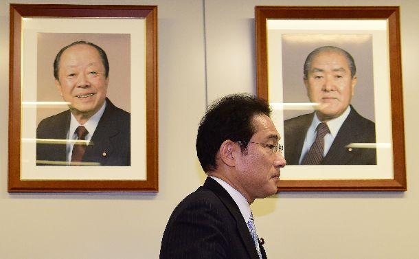 自民党総裁選への不出馬会見の後、退出する岸田文雄政調会長。宏池会出身の宮沢喜一元首相(左)、鈴木善幸元首相の顔写真が壁に飾られていた=2018年7月24日