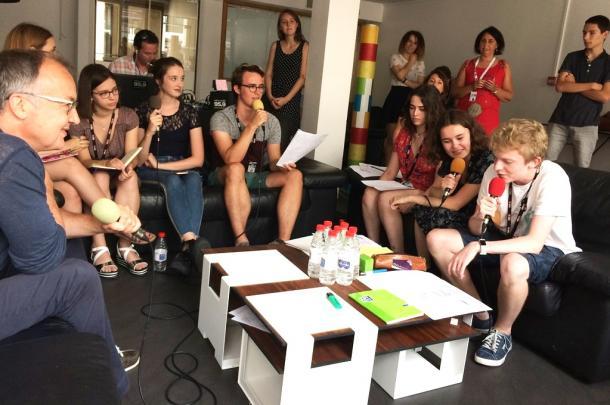 高校生たちが映画祭をリポートする生番組を収録中。  フランスの実力派フィリップ・フォコン監督(左)のインタビューに挑戦だ