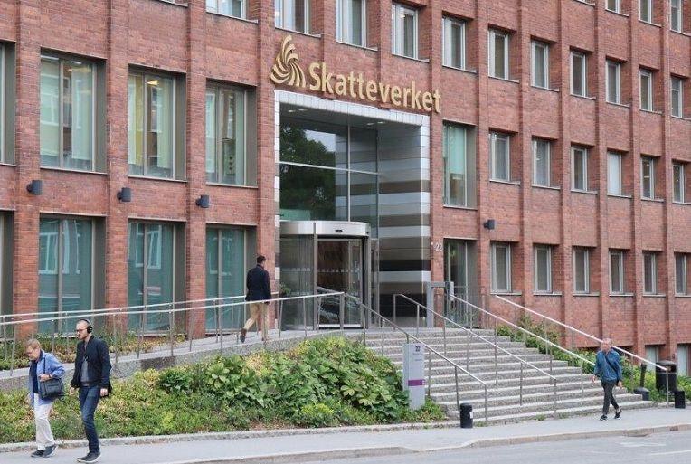 写真・図版 : スウェーデンの国税庁の建物には3枚の羽根のロゴがある。街の税務署にも同じロゴが掲げられている=ソールナ市