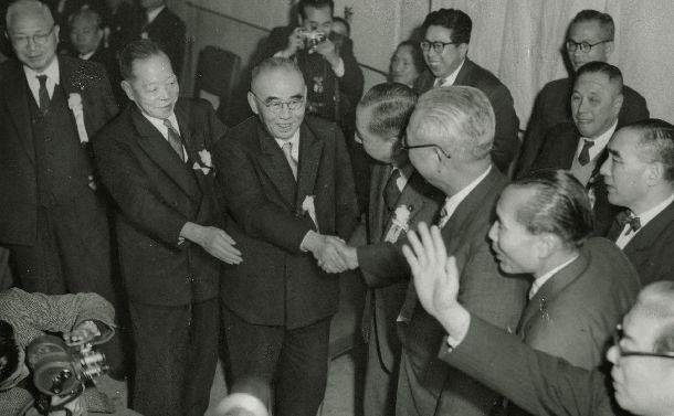 1956年の自民党総裁選で新総裁になった石橋湛山氏(中央)と握手する、破れた岸信介幹事長(その右)ら