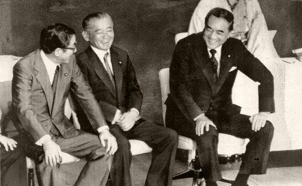 写真・図版 : 自民党党総裁としての任期を1年間延長することを両院議員総会で満場一致で決めて笑う中曽根康弘首相(右)。中央は竹下登幹事長、左は安倍晋太郎総務会長 =1986年9月11日