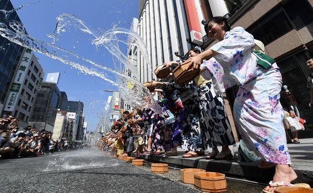 写真・図版 : 合図に合わせて一斉に打ち水をする人たち=2018年8月5日、東京・銀座