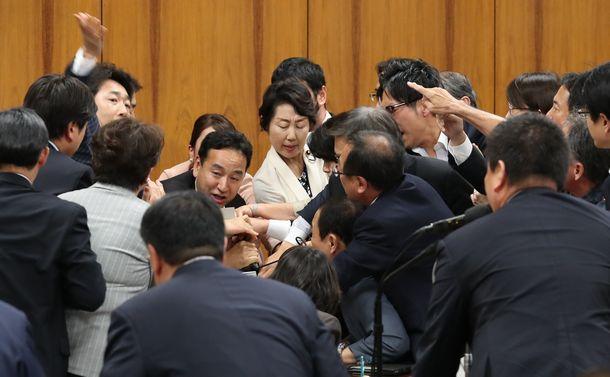 写真・図版 : 衆院内閣委でカジノ実施法案の採決が進められ、山際大志郎委員長(中央左)に詰め寄る野党委員ら。手前は起立する与党委員=2018年6月15日