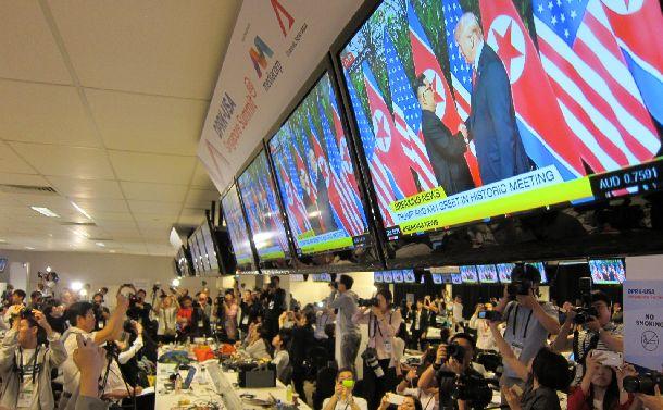 写真・図版 : シンガポールのメディアセンターのモニターに映し出される米朝両首脳の握手の瞬間=2018年6月12日