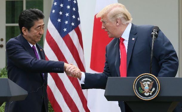 写真・図版 : 共同記者会見で握手するトランプ米大統領(右)と安倍晋三首相=2018年6月7日、ワシントンのホワイトハウス