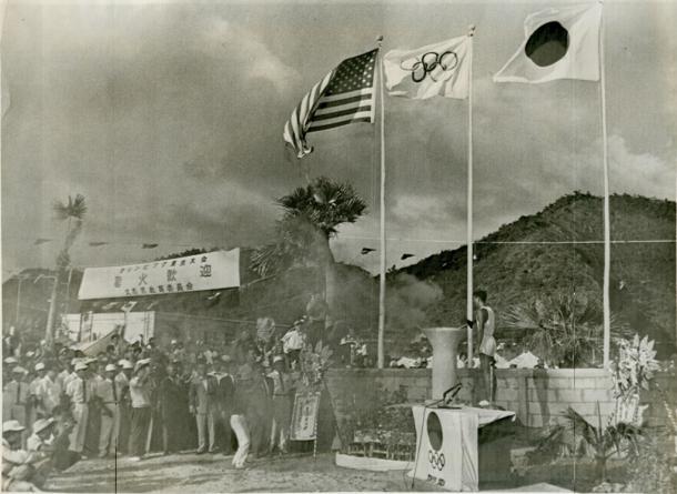 1964年9月4日 東京五輪 米国統治下の沖縄 やんばるの聖火リレー 沖縄・久志村(現名護市) 嘉陽小中学校の聖火台に点火する徳村政勝走者 オリンピック写真協会/代表撮影