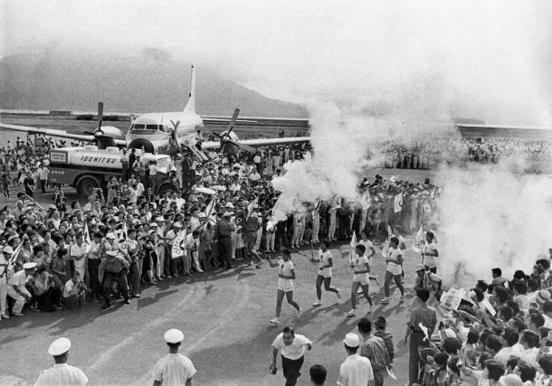 沖縄から聖火が本土に到着、始まった聖火リレー・先頭は高橋律子走者。後方は歓迎の人たちと空輸にあたった全日空「聖火号」(YS-11)