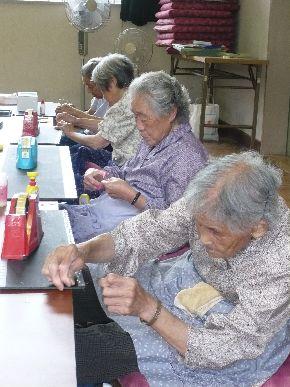「enishi」の制作を手伝うご婦人たち(手前より80代、70代、60代、50代)。のべ400人が制作に携わった