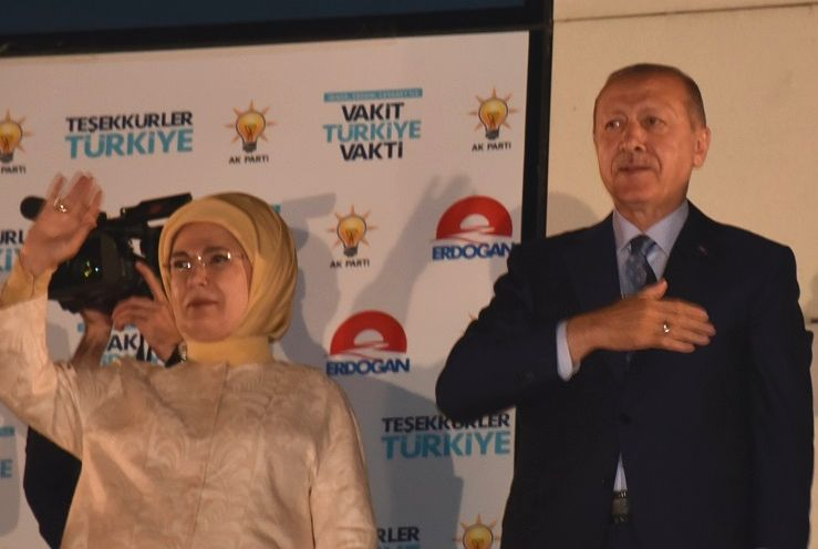 写真・図版 : トルコの首都アンカラにある与党・公正発展党本部で、支持者に感謝を表すエルドアン大統領(右)とエミネ夫人=2018年6月25日、アンカラ