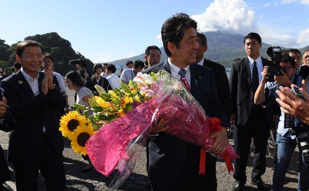 写真・図版 : 自民党総裁選への立候補を表明後、花束を受け取り、笑顔を見せる安倍晋三総裁=8月26日、鹿児島県垂水市