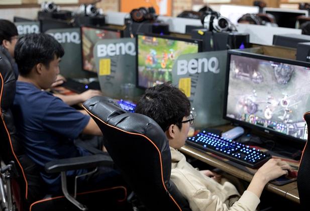 写真・図版 : 長時間プレーによる死亡事件が起きて社会問題になった韓国では、PC房(バン)が人気だ。大画面モニターのPCと椅子がずらりと並び、若い男性らがオンラインゲームを楽しむ=2017年9月30日、韓国始興市、野上英文撮影