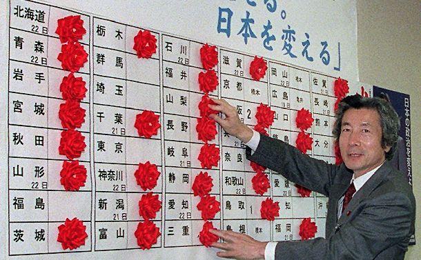 自民党総裁予備選で勝った地区にバラの花をつける小泉純一郎氏。地方での地滑り的な大勝で総裁の座に就く=2001年4月23日、自民党本部で