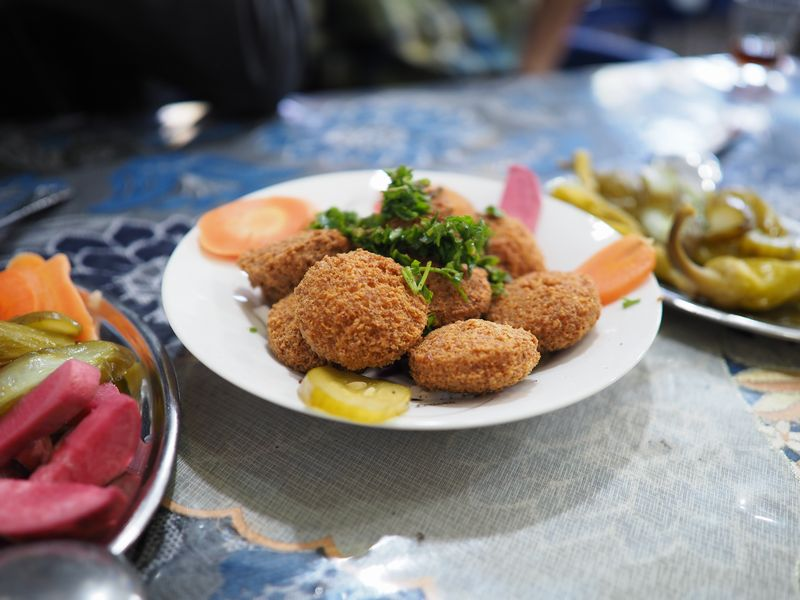 写真・図版 : 朝食で頂いたファラーフェル。野菜の漬物やひよこ豆のペーストなどと一緒に頂く