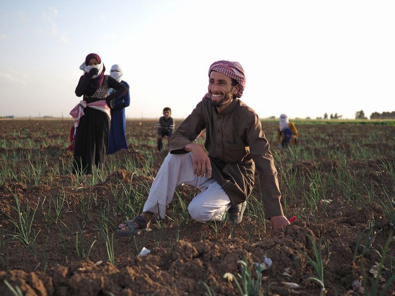 写真・図版 : アムダ郊外の村で。「今年は雨が少ない」と心配しつつ、畑仕事に精を出す家族たち