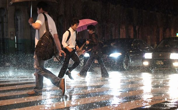 台風の影響で雨が強くなり、走って横断歩道を渡る人たち=2018年8月23日