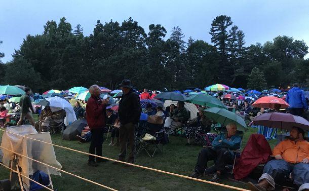 写真・図版 : 土砂降りの中ジョンウィリアムスの公演のため芝生に場所取りする人々