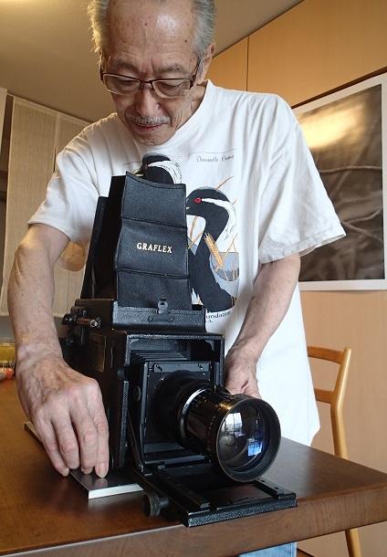 写真・図版 : 塚本洋三さん。下村兼史が愛用したものと同型のグラフレックスカメラ(ガラス乾板で撮影できる)を持ち出して語ってくれた