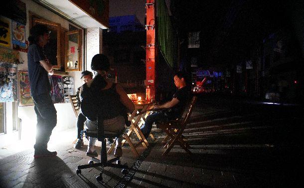 停電が続く札幌の繁華街でろうそくとランタンの明かりの中、ラジオニュースを聞く人たち=2018年9月6日、札幌市中央区