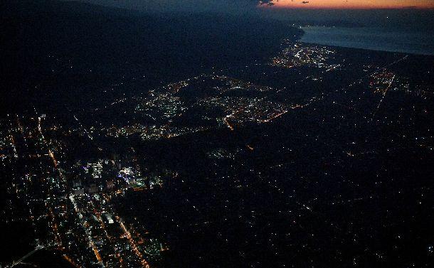 写真・図版 : 夜を迎え停電したままの札幌市内の住宅地(右)。JR札幌駅周辺(中央左)も暗いままだ=2018年9月6日