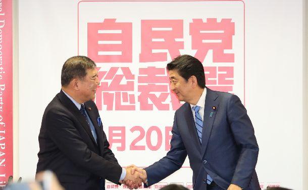 自民党総裁選の記者会見の最後に握手をする石破茂氏(左)と安倍晋三首相=2018年9月10日