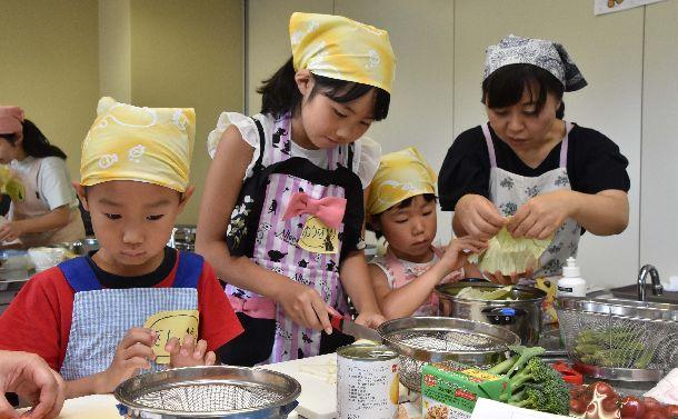 写真・図版 : 働く母子家庭を対象にした料理教室で大人に指導を受けながら、料理をする小学生たち=2017年7月30日、新潟市