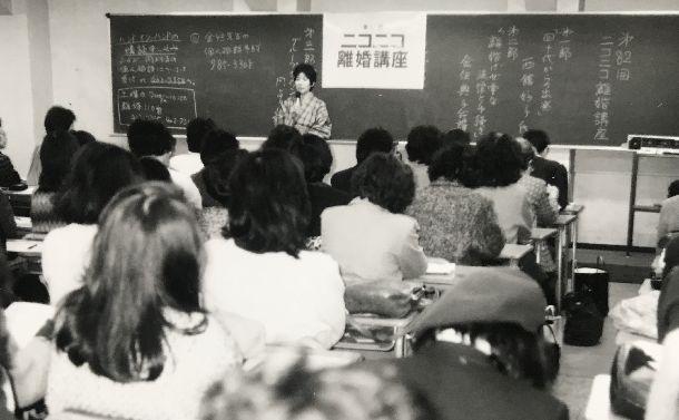 写真・図版 : 東京・原宿で開かれたニコニコ離婚講座で講師を務める井上好子さん。作家の故井上ひさし氏と離婚した直後で100人以上が集まった。月一回の離婚講座には全国から悩める人が集まった=1987年1月31日、筆者提供
