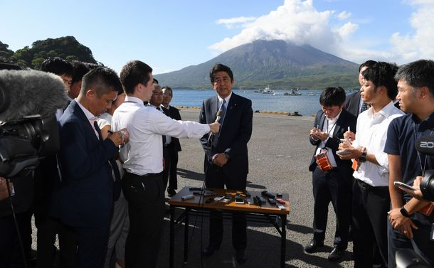 写真・図版 : 桜島を背景に自民党総裁選への立候補を表明する安倍晋三総裁=2018年8月26日、鹿児島県垂水市