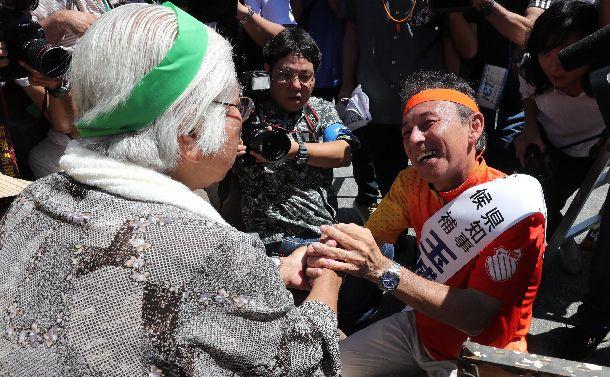 写真・図版 : 沖縄県知事選で支持者と握手する玉城デニー氏=2018年9月13日