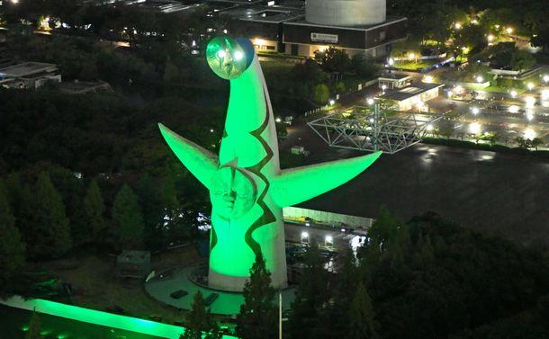 写真・図版 : 臓器移植法の施行から20年、緑色にライトアップされた太陽の塔=2017年10月16日、大阪府吹田市