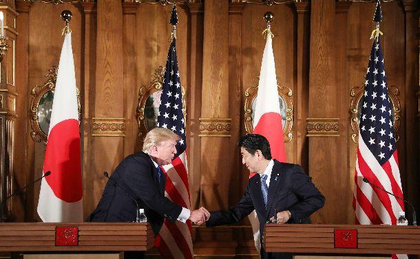 写真・図版 : 共同記者会見で握手する米国のトランプ大統領(左)と安倍晋三首相=2017年11月6日
