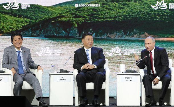 写真・図版 : 東方経済フォーラムの全体会合に臨む(左から)安倍晋三首相、中国の習近平国家主席、ロシアのプーチン大統領=2018年9月12日