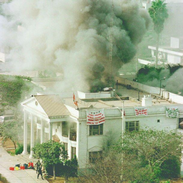 写真・図版 : 特殊部隊が突入して銃撃戦を展開、煙を噴き上げる日本大使公邸=1997年4月22日、リマ