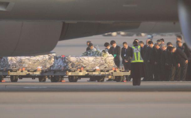 写真・図版 : 政府専用機から降ろされたひつぎに花を手向け、祈る日揮や政府の関係者ら=2013年1月25日、羽田空港