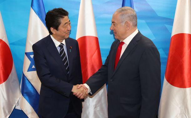 写真・図版 : イスラエルの首相府でネタニヤフ首相(右)の出迎えを受け、握手する安倍晋三首相=2018年5月2日、エルサレム