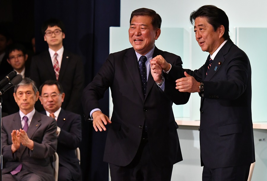 写真・図版 : 自民党総裁選で3選が決まり、石破氏と手を取り合う安倍首相=2018年9月20日、自民党本部