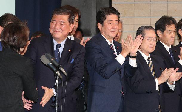 総裁に選ばれた後の自民党両院議員総会で拍手する安倍晋三首相(中央)。左隣は石破茂元幹事長=2018年9月20日、東京・永田町
