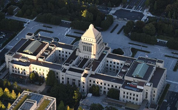 写真・図版 : 夕日を浴びる国会議事堂。日本の政治はどこにいくのか。