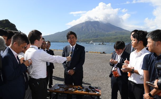 桜島を背景に自民党総裁選への立候補を表明する安倍晋三総裁=2018年8月26日、鹿児島県垂水市