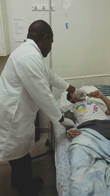 写真・図版 : 病院に運ばれ、医師に診察される筆者。同居人のクリスが撮影していた