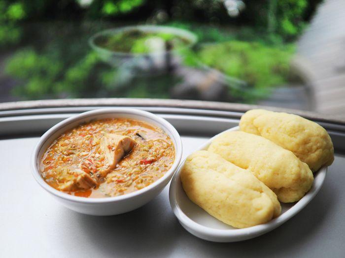 写真・図版 : 家庭料理の一つ、トマト味のきいたオクラスープと主食のフフ(写真はいずれも筆者撮影)