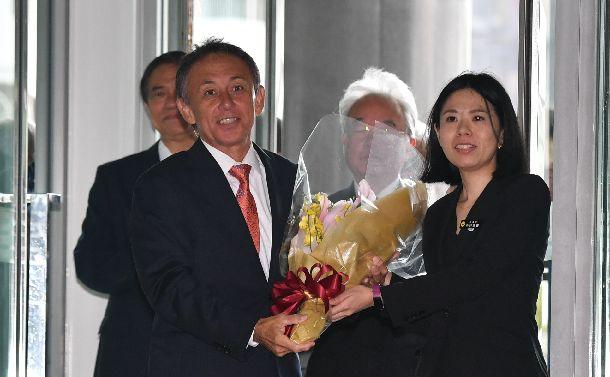 沖縄県庁に初登庁し、職員から花束を受け取る玉城デニー氏(左)=2018年10月4日、那覇市