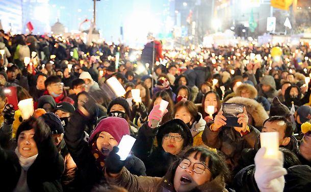 写真・図版 : 韓国の朴槿恵大統領の辞任を求める集会。参加者はろうそくを手にシュプレヒコールを繰り返した=2016年11月26日