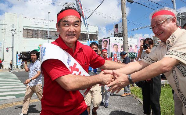 写真・図版 : 沖縄県知事選で支持者と握手をする佐喜真淳氏=2018年9月13日、沖縄県宜野湾市