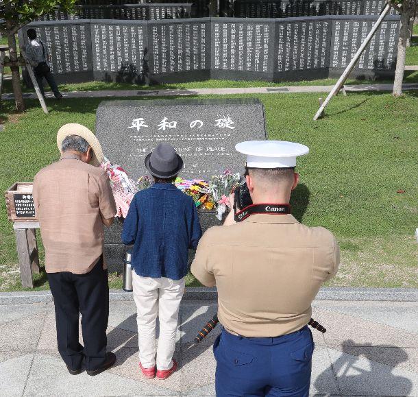 慰霊の日に平和の礎を訪れた人たちを米兵も撮影していた=2018年6月23日、沖縄県糸満市の平和祈念公園
