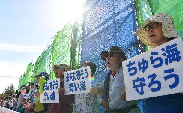 名護市辺野古にある米軍キャンプ・シュワブのゲートのフェンスの前で、プラカードを掲げ移設反対を訴える人たち=2018年8月17日、沖縄県名護市